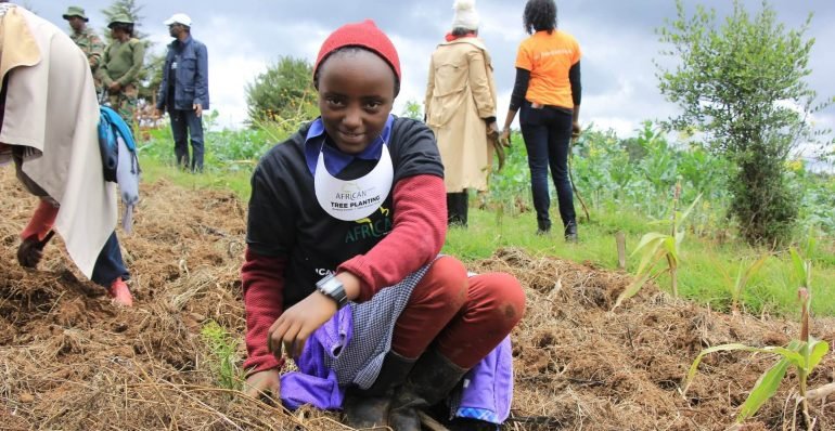 A Photo of a primary school girl planting a tree